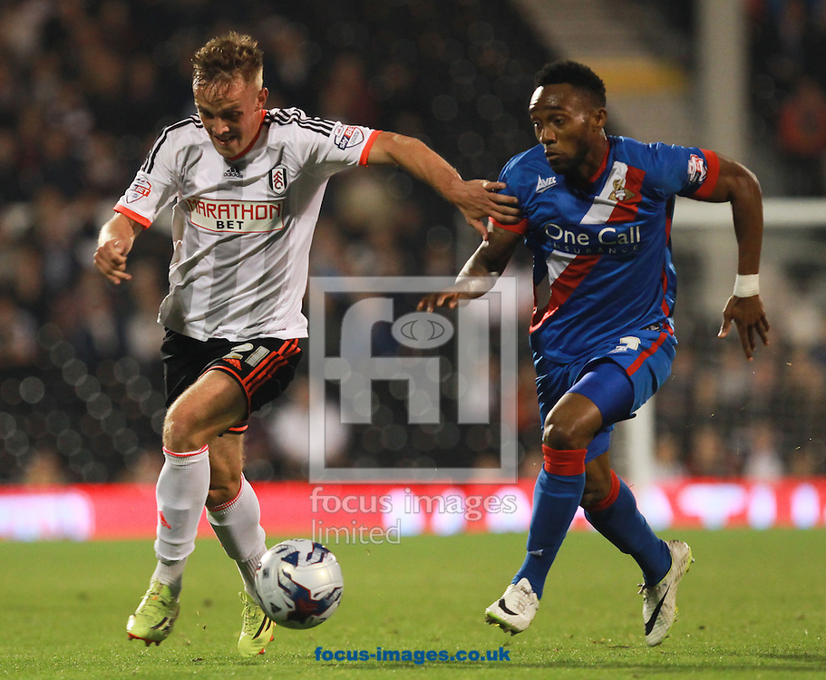 Lasse Vigen Christensen of Fulham and Cedric Evina of Doncaster Rovers during the Capital One Cup match at Craven Cottage, London<br /> Picture by John Rainford/Focus Images Ltd +44 7506 538356<br /> 23/09/2014