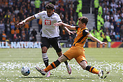 Derby defender Cyrus Christie rides out a challenge by Hull defender Andrew Robertson during the Sky Bet Championship play-off first leg match between Derby County and Hull City at the iPro Stadium, Derby, England on 14 May 2016. Photo by Aaron  Lupton.