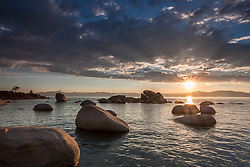 """Sunset at Whale Beach, Tahoe 2"" - Photograph of a sunset at Whale Beach on the East Shore of Lake Tahoe. A man standing on a rock and Whale Rock can be seen in the distance."