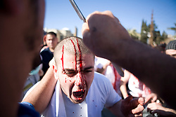 In preparation to march, celebrators cut their heads, some with razor blades and some with larger knives or swords.