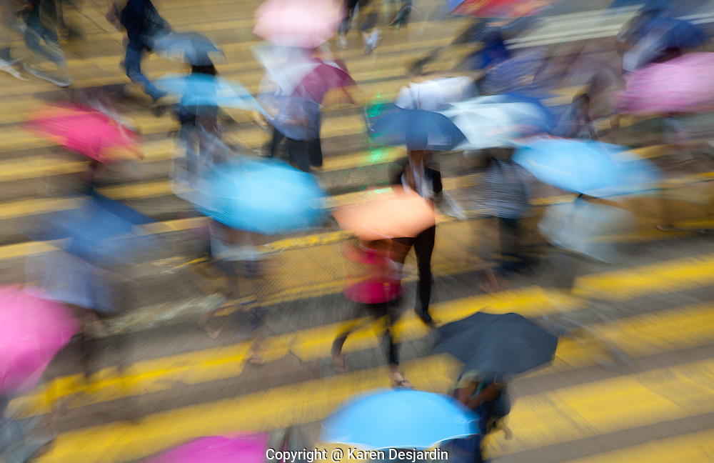 Pedestrians carry umbrellas as they cross a street in the Central district of Hong Kong during a rain shower. http://www.gettyimages.com/detail/photo/rainy-urban-scene-with-motion-blur-hong-high-res-stock-photography/149628336