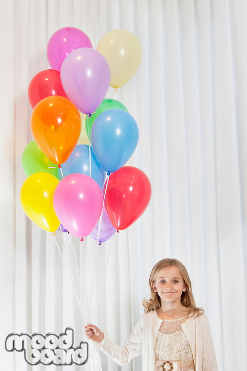 Portrait of young birthday girl standing with party balloons