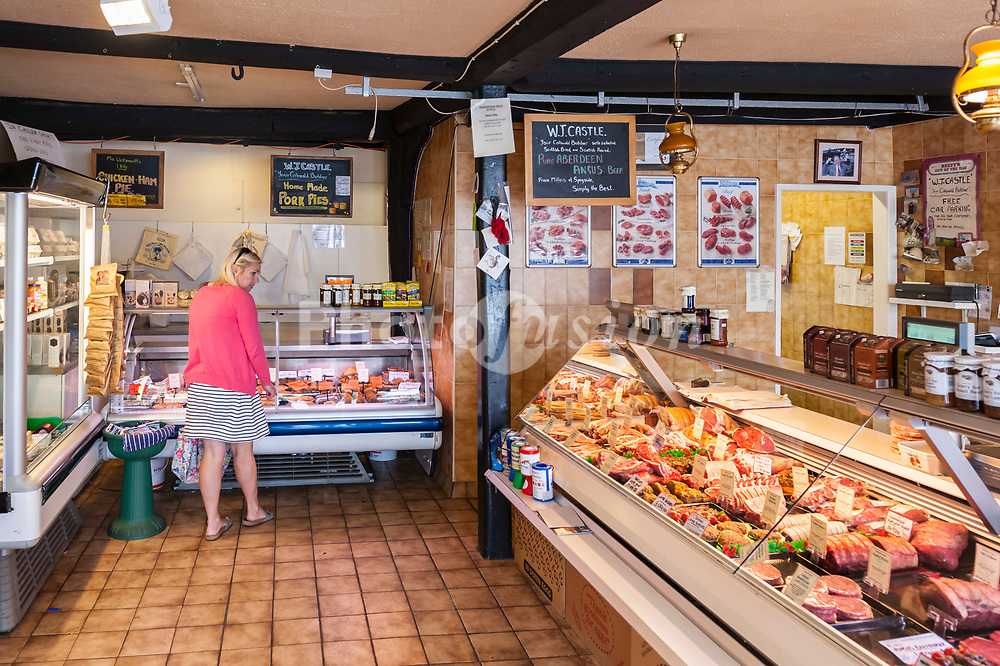 A woman in her 30's shopping in a butchers shop store in the Uk