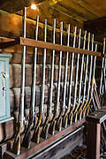 """Flintlock rifles in Kuskov House, Fort Ross, former Russian colony 1812-1842, California, USA. Kuskov House is the reconstructed residence of the founder and first manager of Fort Ross. Living quarters are upstairs above an armory. Fort Ross State Historic Park preserves a former Russian colony (1812-1842) on the west coast of North America, in what is now Sonoma County, California, USA. The 5.5-inch howitzer cannons are historical reproductions. Visit Fort Ross and dramatic coastal scenery 11 miles north of Jenner on California Highway One.  Initially, sea otter pelts funded Russian expansion, but by 1820, overhunting motivated the Russian-American Company to introduce moratoriums on hunting seals and otters, the first marine-mammal conservation laws in the Pacific. Russian voyages greatly expanded California's scientific knowledge. For centuries before Europeans arrived, this site was called Metini and had been occupied by the Kashaya band of Pomo people who wove intricate baskets and harvested sea life, plants, acorns, deer, and small mammals. Sponsored by the Russian Empire, """"Settlement Ross"""" was multicultural, built mostly by Alaskan Alutiiq natives and occupied mostly by native Siberians, Alaskans, Hawaiians, Californians, and mixed Europeans. Renamed """"Ross"""" in 1812 in honor of Imperial Russian (Rossiia), Fortress Ross was intended to grow wheat and other crops to feed Russians living in Alaska, but after 30 years was found to be unsustainable. Fort Ross was sold to John Sutter in 1841, and his trusted assistant John Bidwell transported its hardware and animals to Sutter's Fort in the Sacramento Valley. Fort Ross is a landmark in European imperialism, which brought Spanish expanding west across the Atlantic Ocean and Russians spreading east across Siberia and the Pacific Ocean. In the early 1800s, Russians coming from the north met Spanish coming from the south along the Pacific Coast of California, followed by the USA arriving from the east in 1846 for the Me"""