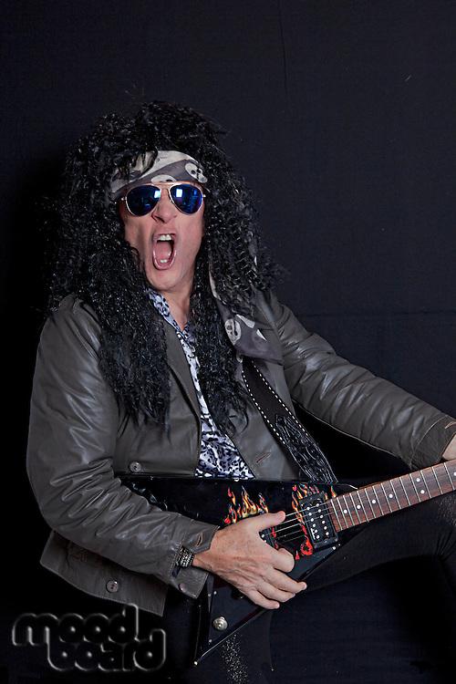 Senior rock guitarist performing over black background