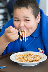 Secondary School student eating spaghetti Bolognese in the Restaurant,