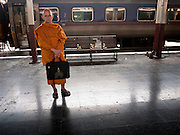 11 JULY 2011 - BANGKOK, THAILAND:   A Buddhist monk waits to board a train in Hua Lamphong train station in Bangkok. Hua Lamphong Grand Central Railway Station, officially known as the Bangkok Grand Central Terminal Railway Station, is the main railway station in Bangkok, Thailand. It is located in the center of the city in Pathum Wan District, and is operated by the State Railway of Thailand. The station was opened on 25 June 1916, after six years' construction. The station was built in an Italian Neo-Renaissance style, with decorated wooden roofs and stained glass windows. The architecture is attributed to Turin-born Mario Tamagno, who, with countryman Annibale Rigotti made a mark on early 20th century public building in Bangkok. The pair also designed Bang Khun Prom Palace (1906), Ananda Samakhom Throne Hall in The Royal Plaza (1907-15) and Suan Kularb Residential Hall and Throne Hall in Dusit Garden, among other buildings..There are 14 platforms and 26 ticket booths. Hua Lamphong serves over 130 trains and approximately 60,000 passengers each day. Thailand has the most advanced rail system in Southeast Asia and trains from Hua Lamphong serve all corners of the Kingdom.        PHOTO BY JACK KURTZ