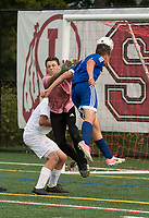 Gilford's Adam Donnelly heads the ball into the net just ahead of Cam Souda's block during NHIAA Division III soccer on Thursday afternoon.  (Karen Bobotas/for the Laconia Daily Sun)