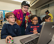 Marty Daniel helps students work a coding exercise during an Hour of Code at Kolter Elementary School, December 10, 2014.
