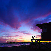 Photo of Lifeguard Tower B and Balboa Pier sunset in Newport Beach California. The sky had beautiful dramatic clouds with a mix of blue, purple, and orange colors. Newport Beach is a popular coastal beach city along the Pacific Ocean in Orange County Southern California. Copyright ⓒ 2017 Paul Velgos with All Rights Reserved.