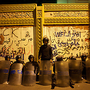 Egyptian National Police takes guard at the presidential palace, in Cairo, where tens of thousands gathered to voice their anger against a planned referendum for a new islamic-based constitution planned by president Mohamed Morsi.