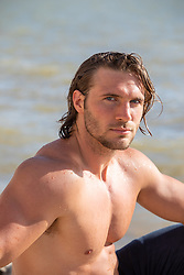 good looking man without a shirt by a lake