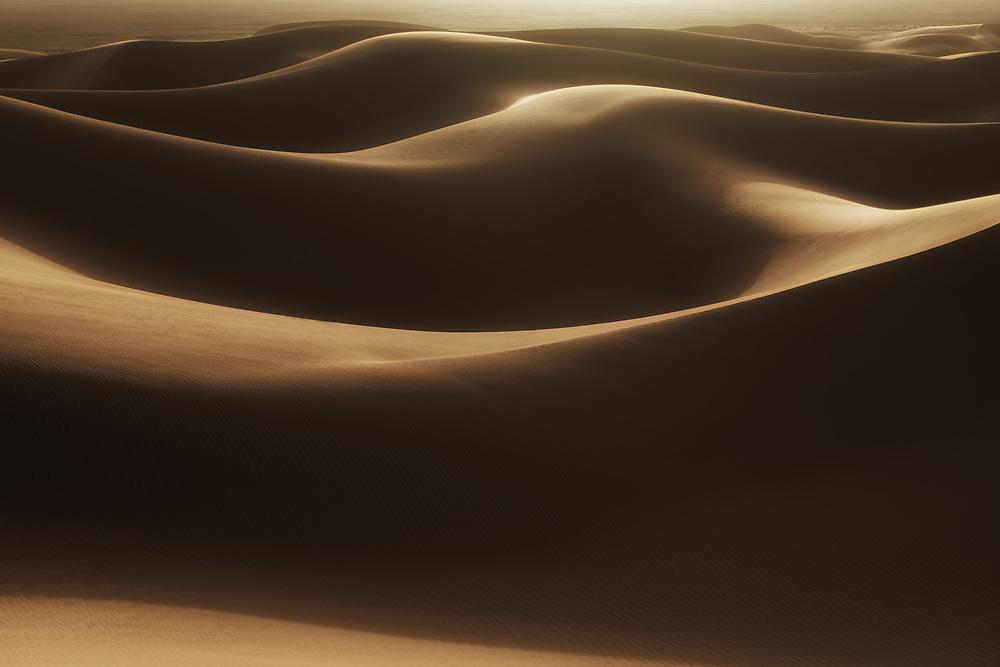 Abstract desert sand dunes with deep shadows, Morocco.