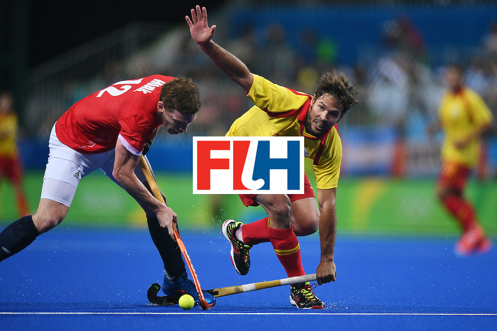 Spain's Pau Quemada (C) and Britain's Michael Hoare vie during the mens's field hockey Britain vs Spain match of the Rio 2016 Olympics Games at the Olympic Hockey Centre in Rio de Janeiro on August, 12 2016. / AFP / MANAN VATSYAYANA        (Photo credit should read MANAN VATSYAYANA/AFP/Getty Images)