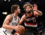 Brooklyn Nets center Brook Lopez (11) takes aim for the basket around his twin brother, Portland Trail Blazers center Robin Lopez (42) in the second half of an NBA basketball game on Monday, April 6, 2015, in New York. (AP Photo/Kathy Kmonicek)