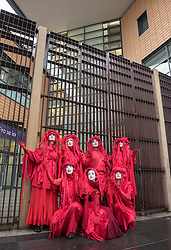 © Licensed to London News Pictures. 19/07/2019; Bristol, UK. Extinction Rebellion Summer Uprising 2019. The Red Brigade from Extinction Rebellion, representing the blood of species that have and will become extinct due to climate change, attend Bristol Magistrates Court in support of 16 people who are appearing at court after being arrested on Wednesday when they blocked a major road junction at the end of the M32 into Bristol which caused major traffic disruption. Campaigners locked themselves onto a pink bath tub, and held 7 minute roadblocks on other parts of the junction complex. Extinction Rebellion are holding a five-day 'occupation' of Bristol, by occupying Bristol Bridge in the city centre and traffic has to be diverted and carrying out other events. As part of a country-wide rebellion called Summer Uprising, followers will be holding protests in five cities across the UK including Bristol on the theme of water and rising sea levels, which is the group's focus for the South West. The campaign wants the Government to change its recently-set target for zero carbon emissions from 2050 to 2025. Photo credit: Simon Chapman/LNP.