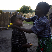 Noria Akushange, the grandmother of Munalula, 8,  puts vaseline on her face as she gets ready for school at sunrise. Munalula, an Aids orphan, is raised by her grandmother, and is too poor to afford the uniform required to attend the local overnment school. The community school the children attend receives rations from the World Food Program, but the ration is scheduled to run out on April 9th unless donors come through with money to buy food locally or find another way of getting food to the community quickly.