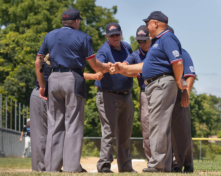 The Umpires gather for a pre-game huddle before the start of the winner take all final of the Eastern Regional Senior League tournament between Pennsylvania and Maryland held in West Deptford on Thursday, August 11.