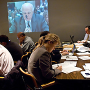 """Press room during the hearing. A live feed of the hearing was projected on the wall. Commission staffers present Staff Statement No. 15, """"Overview of the Enemy."""" The 9/11 Commission's 12th public hearing on """"The 9/11 Plot"""" and """"National Crisis Management"""" was held June 16-17, 2004, in Washington, DC."""