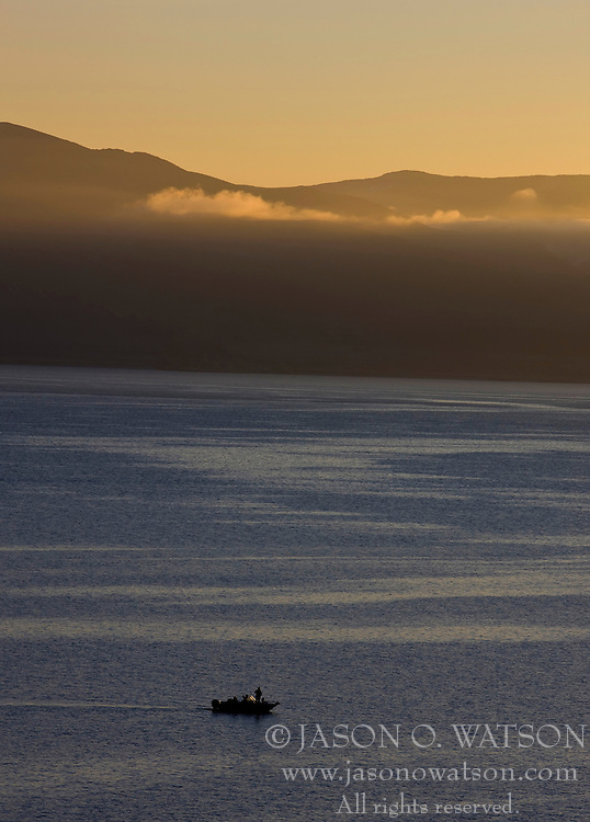 A fisherman in his boat with mountains and gold clouds in the background at sunrise, Pyramid Lake, Nevada.