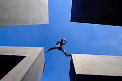 Man jumping between concrete pillars at The memorial to the murdered jews of Europe , Holocaust Memorial, in  Berlin Germany