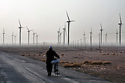 Gansu, China - 26 Feb 2010. A man cycles pass Guazhou wind farm, in Yumen, Gansu province, China. China has set a target for renewable energy consumption of 40 percent of the market by the year 2050.