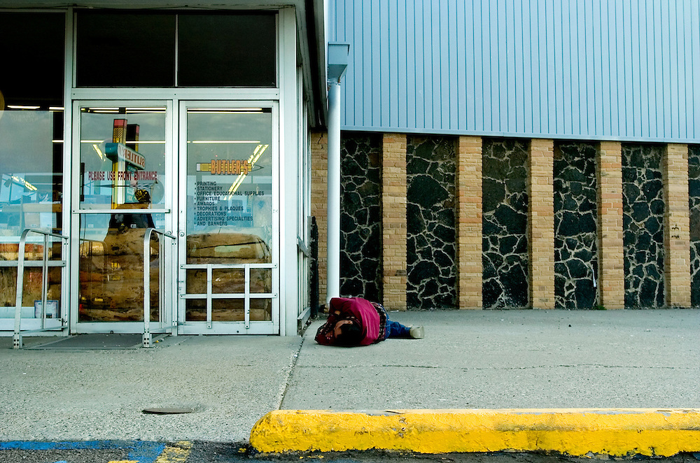 A man lays passed out on a strip mall sidewalk in Gallup, New Mexico. The city was once dubbed Drunk Town USA by 60 Minutes due to its significant problems with alcohol.