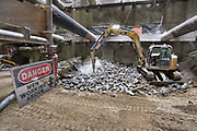 An excavator fitted with a jackhammer breaks apart pieces of tunnel lining segments removed as excavation of the station platform cavern progresses.