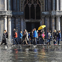 VENICE, ITALY - NOVEMBER 05: Tourists walk on the walkways in Saint Mark's Square during today Acqua Alta on November 5, 2013 in Venice, Italy. The high tide, or acqua alta as it is locally known, is a natural event most commonly affecting the city during Autumn and Winter.  (Photo by Marco Secchi/Getty Images)