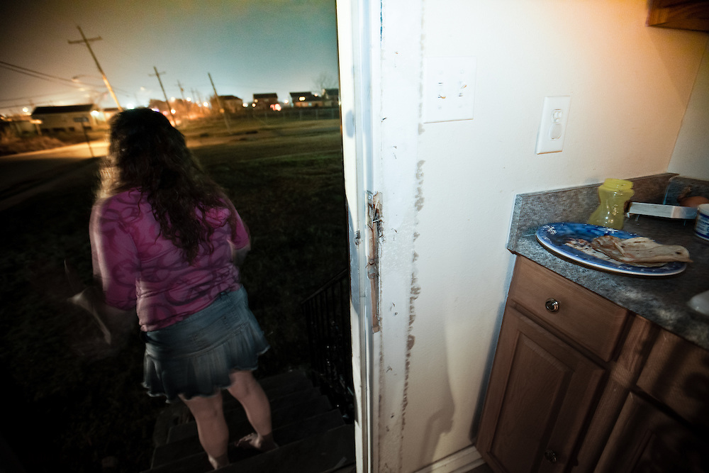 New Orleans Dec. 31, 2011,  Woman watches from her backdoor as Oddicer DeSalvo takes away her boyfriend after breaking up a domestic dispute on New Years Eve. New Orleans crime rate is among the highest in America and is considered to be one of the most dangerous cities in the world.
