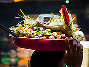 10 OCTOBER 2016 - UBUD, BALI, INDONESIA:  A woman carries a tray of temple offerings on her way to the Hindu temple in the market in Ubud. The morning market in Ubud is for produce and meat and serves local people from about 4:30 AM until about 7:30 AM. As the morning progresses the local vendors pack up and leave and vendors selling tourist curios move in. By about 8:30 AM the market is mostly a tourist market selling curios to tourists. Ubud is Bali's art and cultural center.     PHOTO BY JACK KURTZ