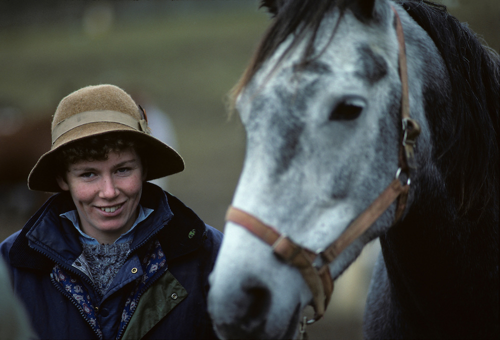 Europe, Ireland, Woman and horse in rain at Ballinasloe Horse Fair in County Galway on autumn afternoon