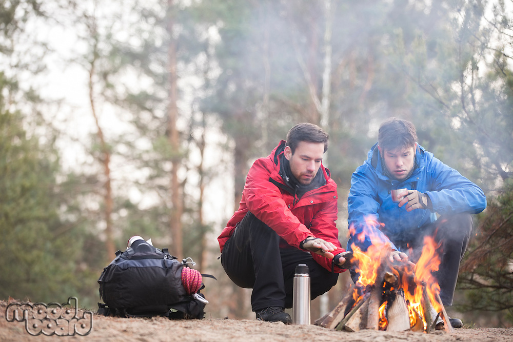 Male hikers warming hands at campfire in forest