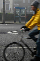 Cyclist on Pembroke Road in Dublin Irelans, two public phone boxes in background