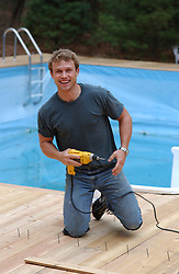 man working on a deck by a pool