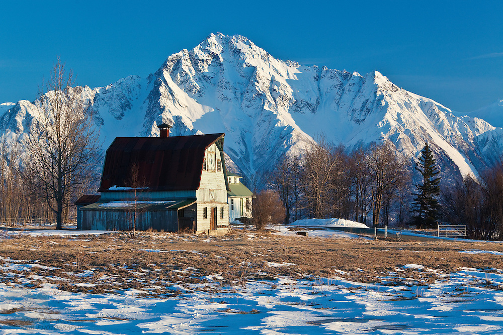 "A colony barn sits atop a hill near Palmer, Alaska, with Pioneer Peak as a backdrop. During President Franklin Delano Roosevelts' presidential term, he implemented the ""New Deal"" where settler's could gain land to develop farming and jobs during the Great Depression of the early 1930's. The Matanuska Valley in Alaska was one of those places where the program developed infrastructure toward these goals."
