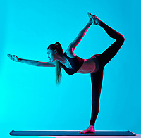 one caucasian woman exercising Natarajasana dancer pose yoga exercices  in silhouette studio isolated on blue background