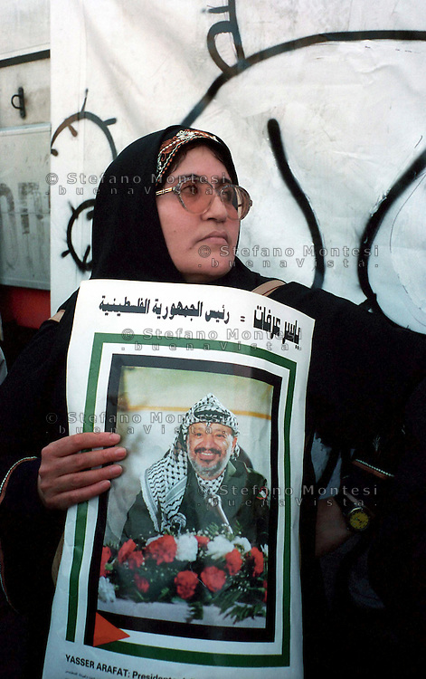 Roma  2004 .Manifestazione per la Palestina.Una manifestante con un cartello con il ritratto di  Yasser Arafat Presidente dell'Autorità Palestinese.Rome 2004.Demonstration for Palestine.A demonstrator,  with a sign bearing a portrait of Palestinian Authority President Yasser Arafat