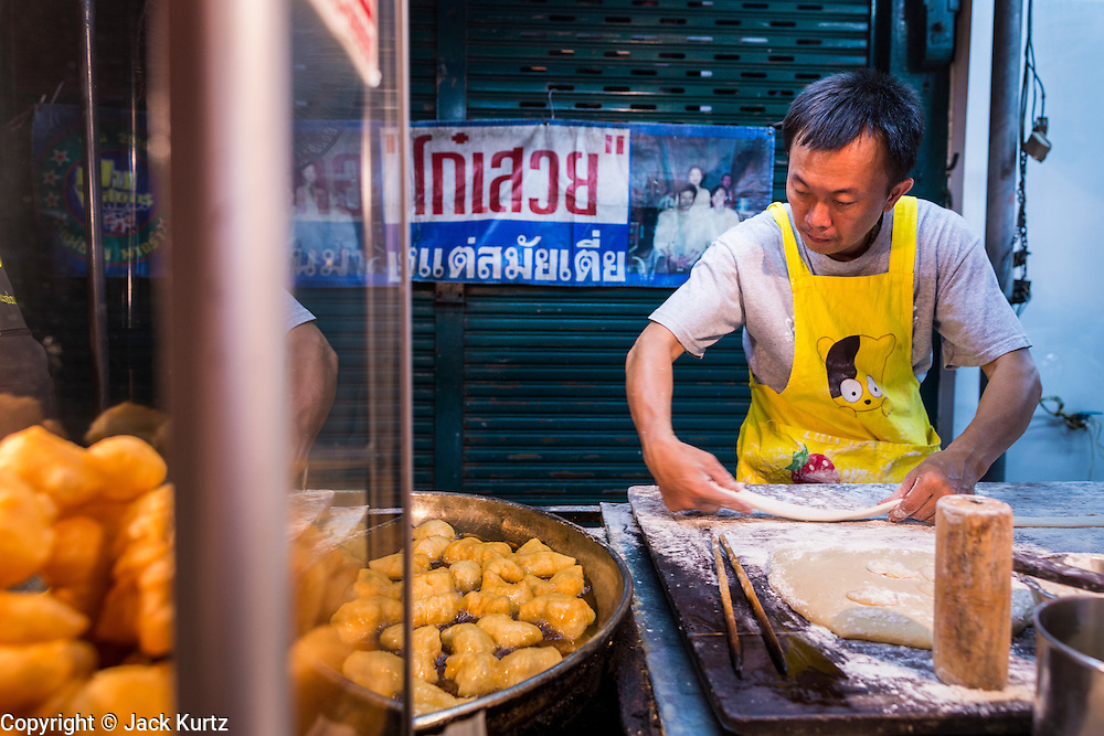18 SEPTEMBER 2013 - BANGKOK, THAILAND:  A man makes Pa thong go, or fried dough sticks (a sort of Thai-Chinese doughnut) at his street stall in the Chinatown section of Bangkok. Thailand in general, and Bangkok in particular, has a vibrant tradition of street food and eating on the run. In recent years, Bangkok's street food has become something of an international landmark and is being written about in glossy travel magazines and in the pages of the New York Times.     PHOTO BY JACK KURTZ