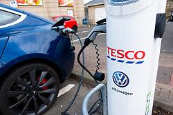 Tesla electric car charging at free charging station in Tesco supermarket, UK, United Kingdom