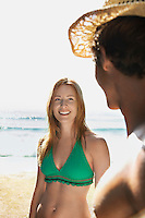 Young woman in bikini smiling at young man at beach half length