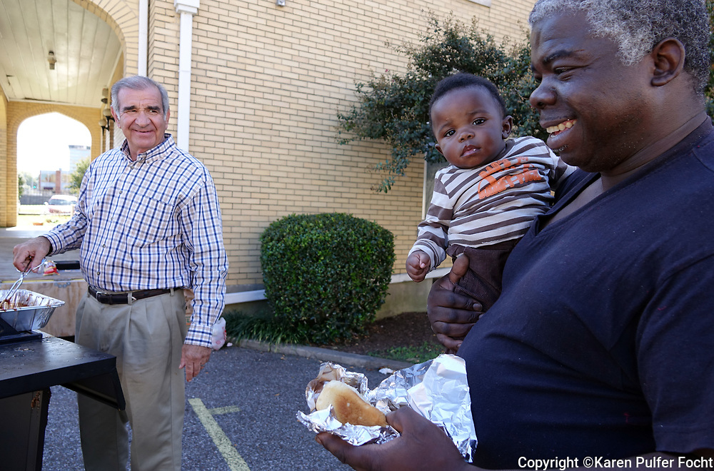 Former Memphis Mayor Dick Hackett  (Left) is the new Executive Director of the Catholic Charities of West Tennessee. Looking to expand their outreach, CCWTN had a cookout in the neighborhood Wednesday.  Hackett serves BBQ hot dogs to the needy.  © Karen Pulfer Focht-ALL RIGHTS RESERVED-NOT FOR USE WITHOUT WRITTEN PERMISSION