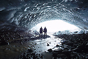 A couple stand at the entrance to an ice cave in the Vatnajokull glacier in south-east Iceland.