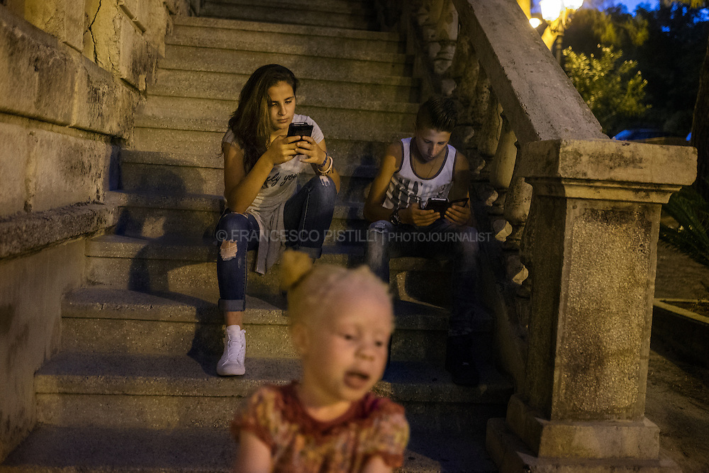 An albino girl escaped from western Africa is playing while locals are chatting on the smartphones. RIACE (ITALY) 04/08/16