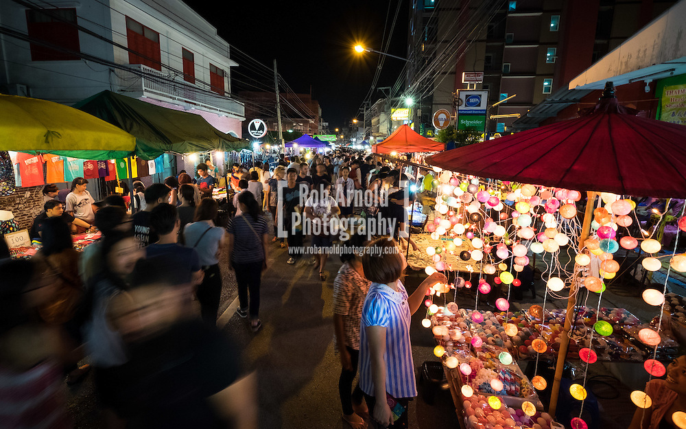 People shopping at the calm and atmospheric walking night market along Wualai Road in Chiang Mai, Thailand.