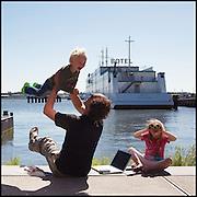 Nederland, Amsterdam, 29-05-2009 - Vader speelt aan de oever van het  Het Ij met zijn twee kleine kinderen tijdens zijn papadag.  Met zijn laptop tussen zich in  houdt hij contact met zijn klanten. Op de achtergrond het Botel. Foto: Gerard Til