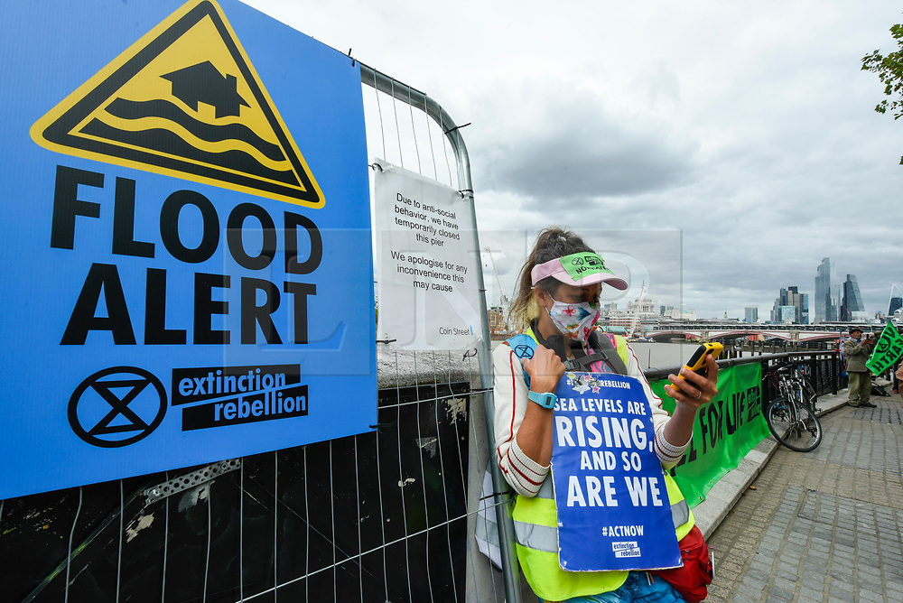 """© Licensed to London News Pictures. 06/09/2020. LONDON, UK.  An activist from Extinction Rebellion (XR) takes part in a """"Flood Alert"""" protest on the shore of the River Thames near Gabriel's Wharf on the South Bank to highlight the effects of climate change on rising sea levels.  Photo credit: Stephen Chung/LNP"""