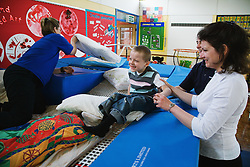 Child with physical disability exercising on soft cushions,