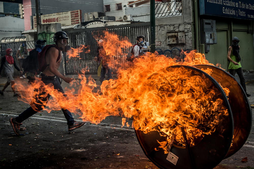 CARACAS, VENEZUELA - JULY 26, 2017: Members of La Resistencia clash with soldiers during an anti-government protest to demand that the National Constituent Assembly election scheduled for Sunday, July 30th be cancelled. The political opposition called for a 48 hour national strike on July 26th and 27th, and for their supporters to close businesses, not go to work, and instead create barricades to block off their streets.  Opposition controlled areas of the country were completely shut down.  The strike was called as part of the opposition's civil resistance movement - that began on April 1st, to protest against the Socialist government's attempt to elect a new assembly that will have the power to re-write the constitution, and their opposition to the Socialist's continued threats to Venezuelan Democracy.  PHOTO: Meridith Kohut for The New York Times