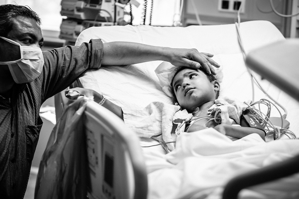 Mariam, 3, comforted by her father before going into operation, children's cancer hospital, Cairo, Egypt.